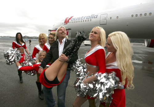 Virgin Chairman Branson carries a cheerleader during a ceremony to mark the delivery of the first Boeing 777-300ER for his new airline V Australia, in Seattle